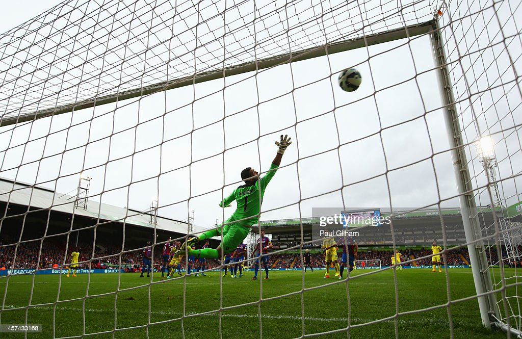 Julian Speroni of Crystal Palace dives in vain as Oscar of Chelsea scores their first goal from a free kick during the Barclays Premier League match between Crystal Palace and Chelsea at Selhurst Park on October 18, 2014 in London, England.
