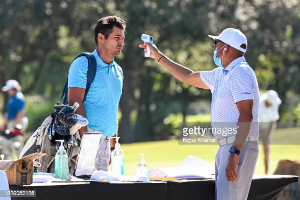 Julian Suri gets his temperature taken as he checks in for the final round of an APGA Tour event on the Slammer Squire Course at World Golf Village...