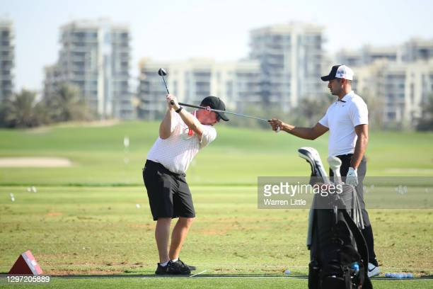 Julian Suri of The United States gives swing advice to caddie during practice ahead of the Abu Dhabi HSBC Championship at Abu Dhabi Golf Club on...