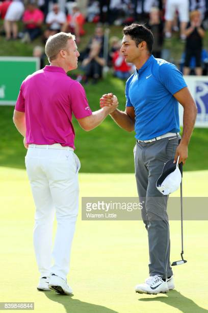 Julian Suri of the United States is congratulated by David Horsey of England on his victory on the 18th green during the final round of Made in...