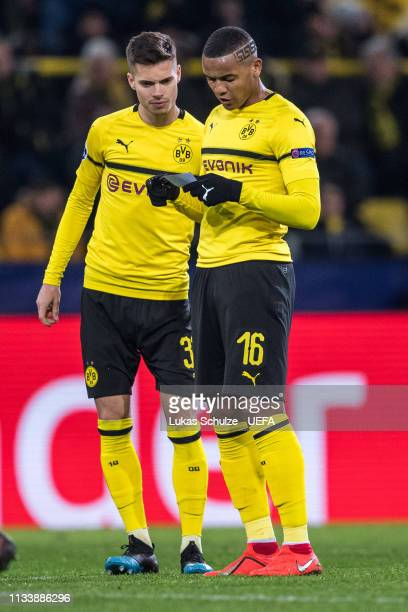 Julian Weigl and Manuel Akanji of Dortmund read notes written by Head Coach Lucien Favre of Dortmund during the UEFA Champions League Round of 16...
