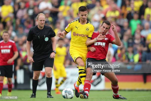 Julian Weigl of Borussia Dortmund challenges Christoph Knoerzer of FC Schweinberg during the preseason friendly match between FC Schweinberg and...