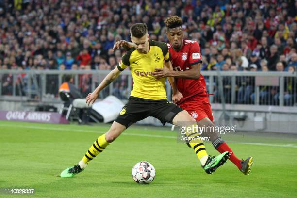 Julian Weigl of Borussia Dortmund is challenged by Kingsley Coman of Bayern Munich during the Bundesliga match between FC Bayern Muenchen and...