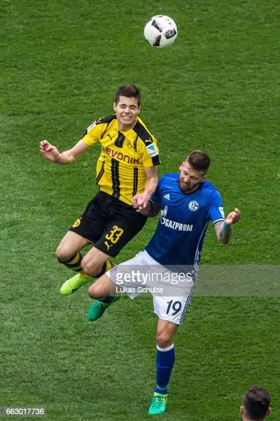 Julian Weigl of Dortmund attacks Guido Burgstaller of Schalke during the Bundesliga match between FC Schalke 04 and Borussia Dortmund at...