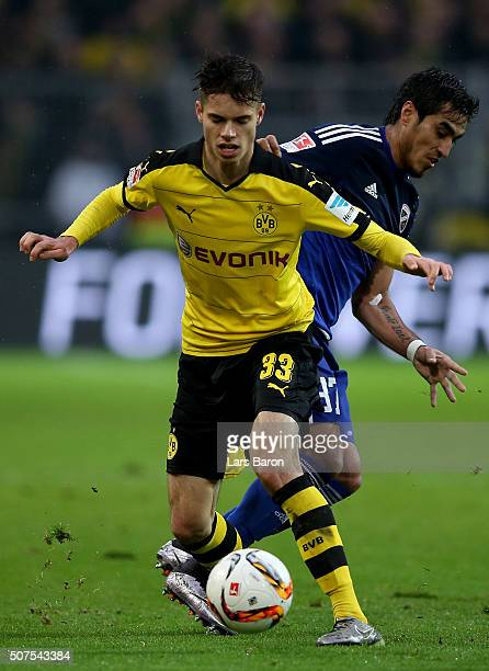 Julian Weigl of Dortmund is challenged by Dario Lezcano of Ingolstadt during the Bundesliga match between Borussia Dortmund and FC Ingolstadt at...