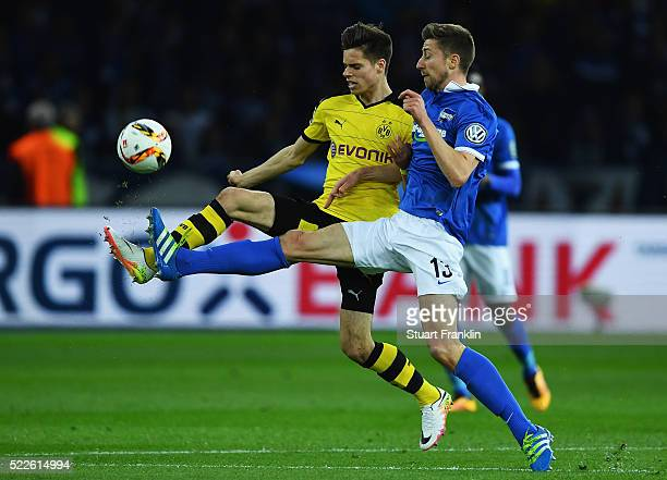 Julian Weigl of Dortmund is challenged by Jens Hegeler of Berlin during the DFB Cup semi final match between Hertha BSC Berlin and Borussia Dortmund...
