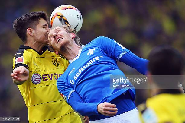 Julian Weigl of Dortmund jumps for a header with Jan Rosenthal of Darmstadt during the Bundesliga match between Borussia Dortmund and SV Darmstadt 98...