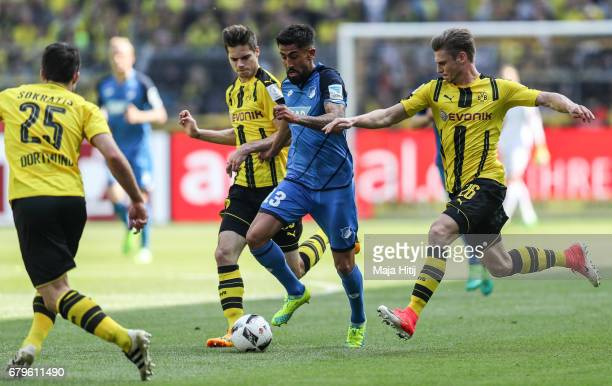Julian Weigl of Dortmund Kerem Demirbay of Hoffenheim and Lukasz Piszczek of Dortmund battle for the ball during the Bundesliga match between...