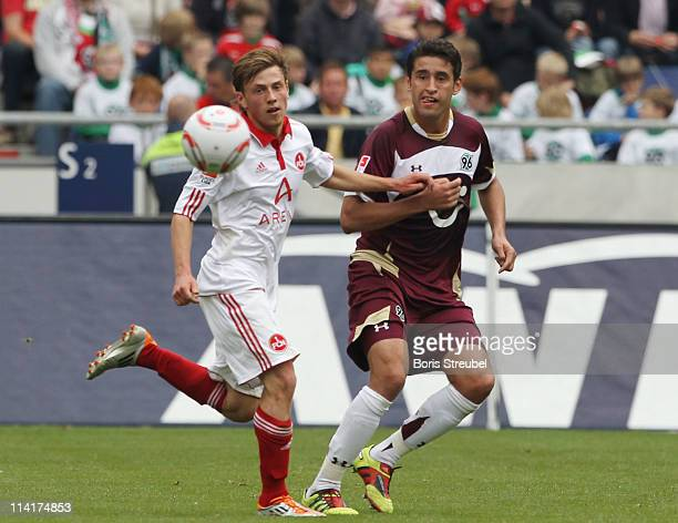 Julian Wiesmeier of Nuernberg battles for the ball with Karim Haggui of Hannover during the Bundesliga match between Hannover 96 and 1 FC Nuernberg...