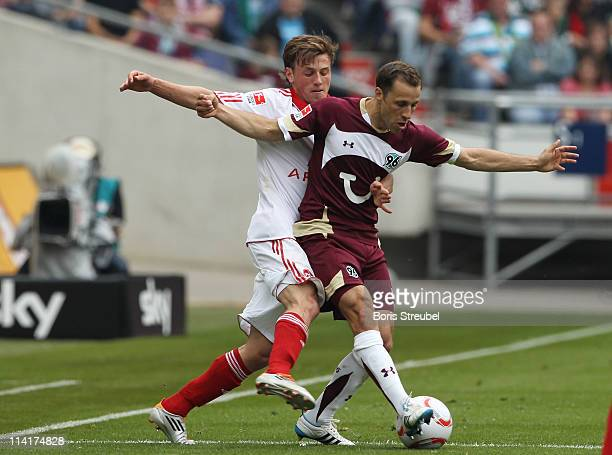 Julian Wiesmeier of Nuernberg battles for the ball with Steven Cherundolo of Hannover during the Bundesliga match between Hannover 96 and 1 FC...
