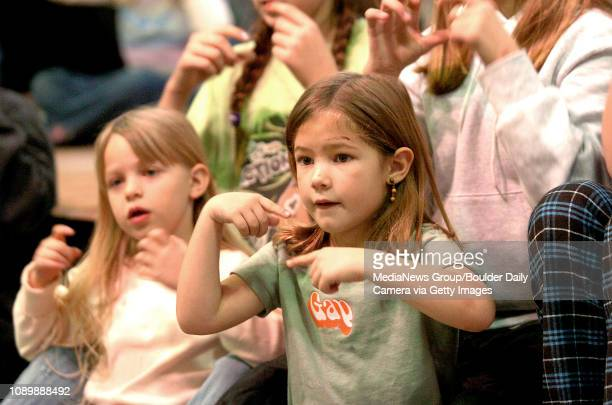 Juliana Watson left and Emma Boelts sing and practice sign language while rehearsing for the school's annual Unicef press conference Tuesday at...