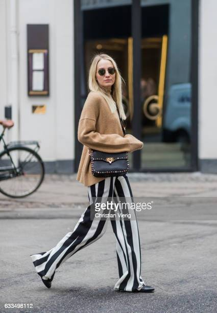 Juliane Diesner wearing a beige Celine sweater Valentino bag Ganni lace top black white striped pants Alice Olivia Gucci shoes at the Copenhagen...