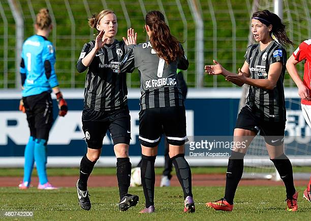 Juliane Maier of Freiburg celebrates her team's second goal with team mates Sara Daebritz and Sylvia Arnold during the Women's DFB Cup Quarter Final...