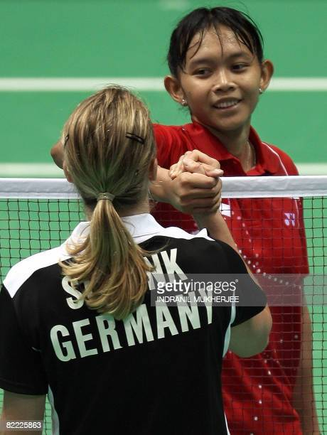 Juliane Schenk of Germany shakes hand with Maria Kristin Yulianti of Indonesia at the end of their women's singles first round badminton match at the...