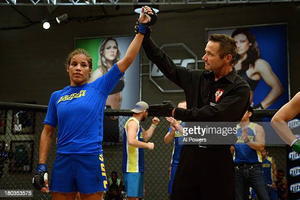 Julianna Pena celebrates after being declared winner against Shayna Baszler by submission in their preliminary fight during filming of season...