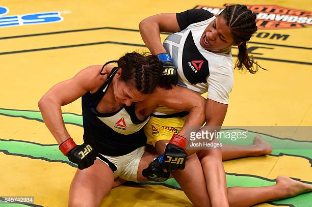 Julianna Pena punches Cat Zingano in their women's bantamweight bout during the UFC 200 event on July 9 2016 at TMobile Arena in Las Vegas Nevada