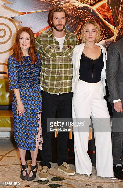 Julianne Moore Liam Hemsworth and Jennifer Lawrence attend a photocall for 'The Hunger Games Mockingjay Part 1' at the Corinthia Hotel London on...