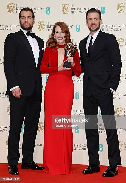 Julianne Moore winner of the Leading Actress award for Still Alice poses with presenters Henry Cavill and Chris Evans in the winners room at the EE...