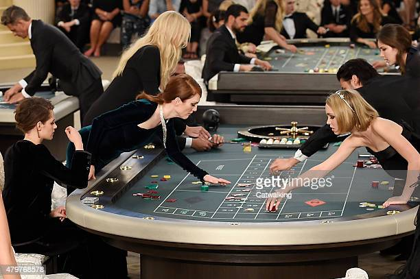 Julianne Moore with Kristen Stewart and Lily-Rose Depp, plays roulette during Karl Lagerfeld's casino presentation at the Grand Palais, Chanel Haute...