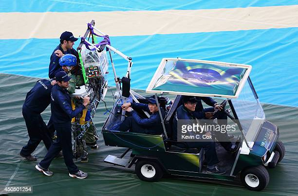 Juliano Pinto in an exoskeleton is helped onto the field during the Opening Ceremony of the 2014 FIFA World Cup Brazil prior to the Group A match...