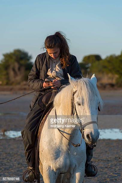 Julie a guardian is texting while riding her horse in the marshlands of the Camargue in southern France