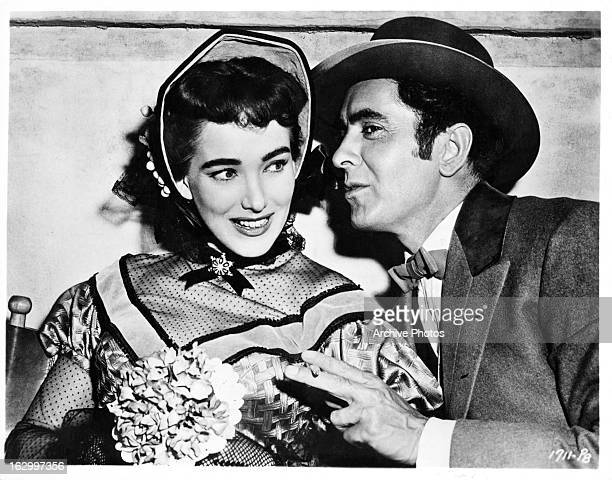 Julie Adams is whispered to by Tyrone Power on set of the film 'The Mississippi Gambler' 1953