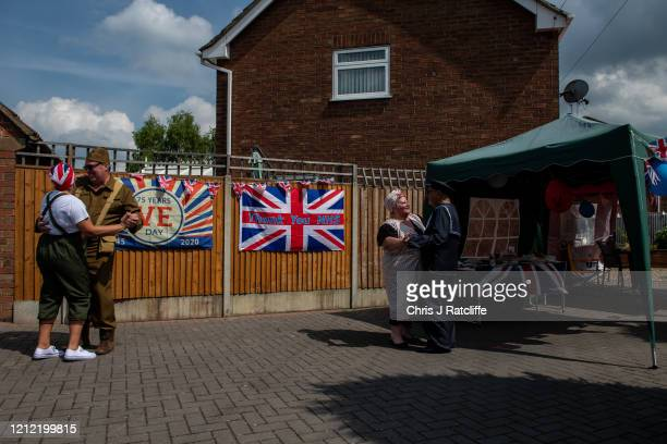 Julie and Jim Hollis dance to 1940s music near Julie and Arthur Williamson who have all dressed up in period costume outside their homes during a...