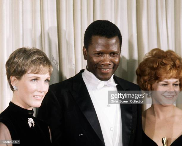 Julie Andrews, British actress, wearing black outfit with a brooch at the neck, Sidney Poitier, Bahamian American actor, wearing a black tuxedo,...