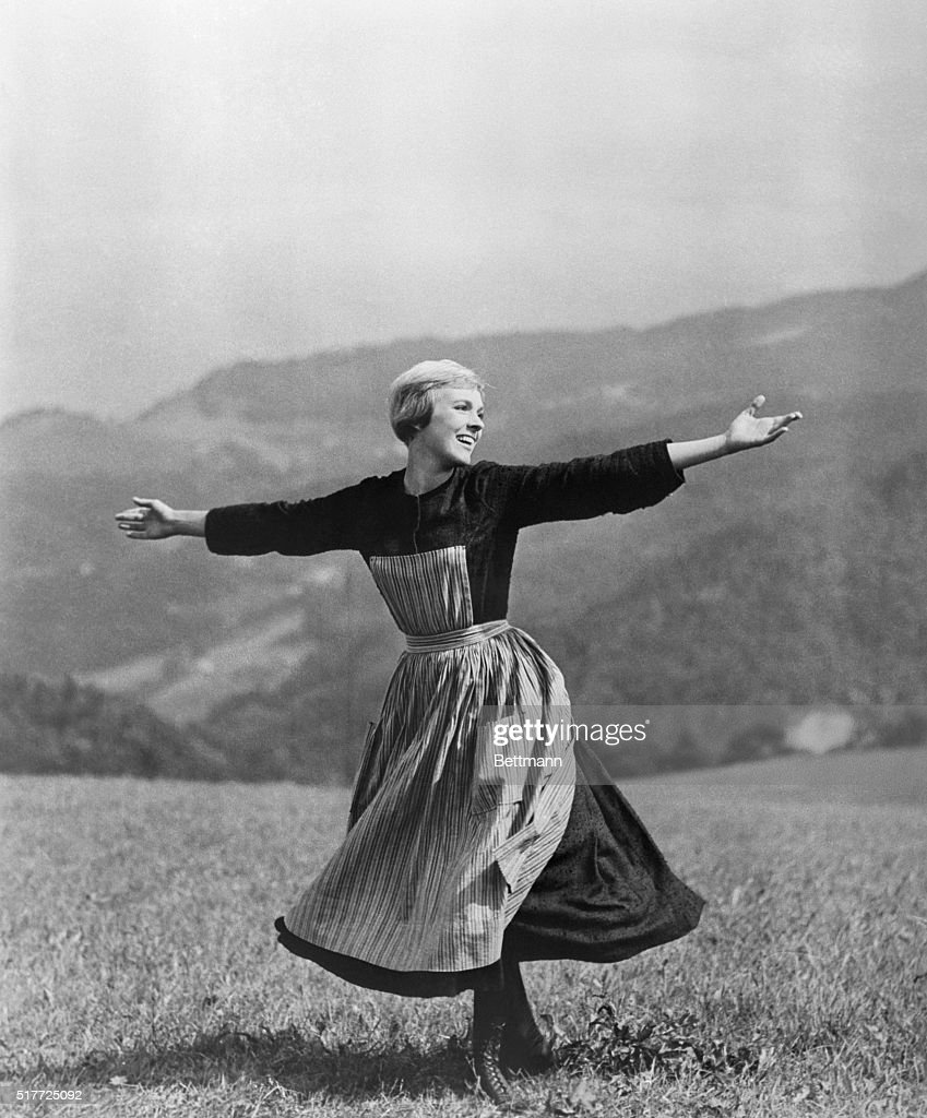 Julie Andrews portrays Maria von Trapp in a scene from the popular movie musical of 1965, The Sound of Music. Andrews, portraying a governess, sings as she sweeps her arms open on a mountain-top.