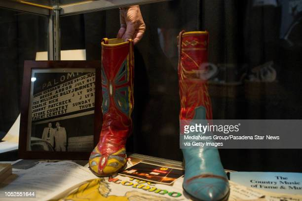 Julie Ann Ream of Valley Relics Museum moves a pair of rhinestonecovered suit designer Nudie Cohn's mismatched boots in a display during a one night...