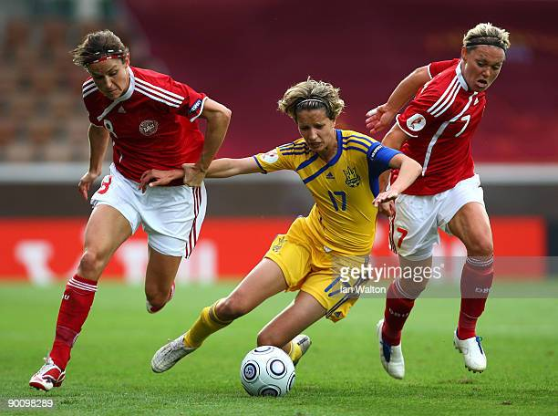 Julie Bukh and Cathrine PaaskeSorensen of Denmark trie to tackle Daria Apanashchenko of Ukraine during the UEFA Women's Euro 2009 group A preliminary...