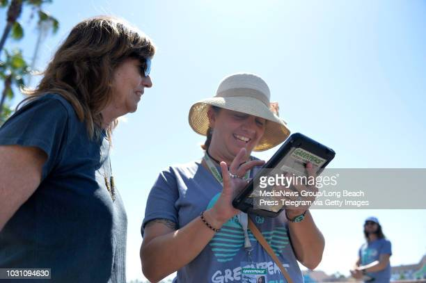 Julie Carey signs up for a membership with Julie Mitchell after she toured the Greenpeace Arctic Sunrise ship docked at Rainbow Harbor in Long Beach...