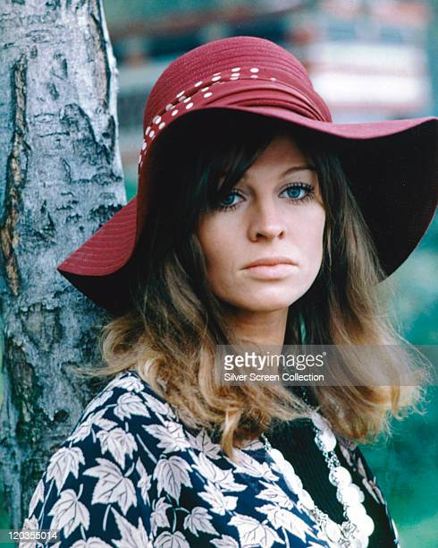 Julie Christie British actress wearing a red floppy widebrimmed hat and a leafprint blouse while posing beside a tree trunk circa 1965