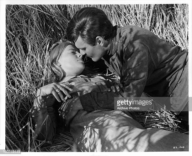 Julie Christie laying in a wheat field with her eyes closed as Omar Sharif leans in to kiss her in a scene from the film 'Doctor Zhivago' 1965