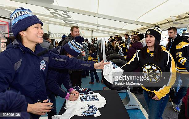 Julie Chu of Les Canadiennes hockey team hands an autographed towel to a fan prior to the 2016 Bridgestone NHL Classic at Gillette Stadium on January...