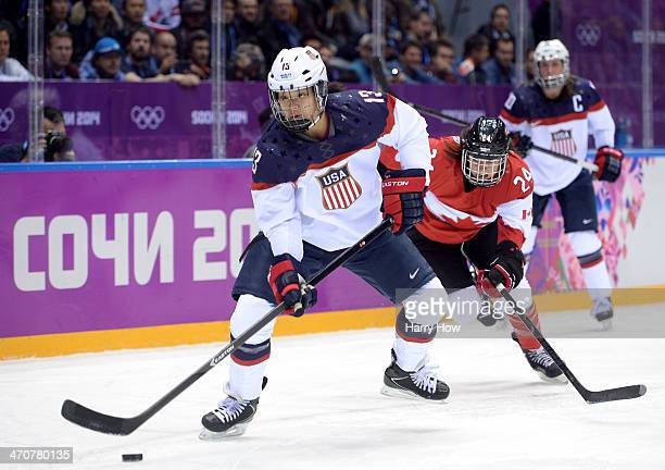 Julie Chu of United States and Natalie Spooner of Canada in action during the Ice Hockey Women's Gold Medal Game on day 13 of the Sochi 2014 Winter...