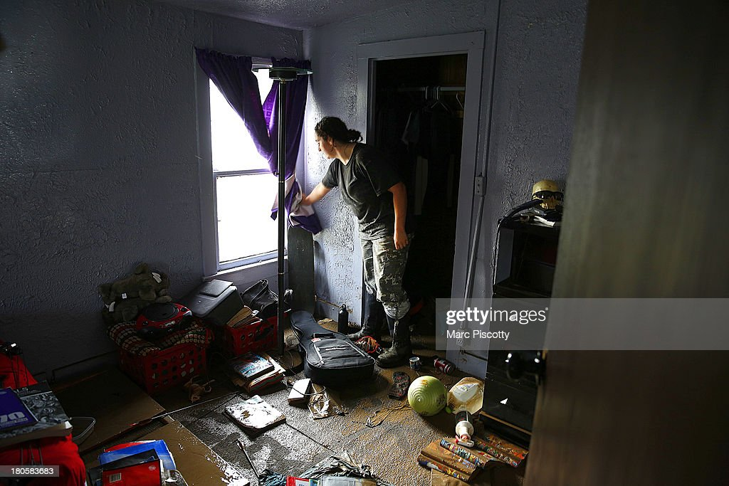 Julie DeGraff pulls back a curtain to reveal the damage inside her home, which had upwards of a foot of standing water inside, on September 14, 2013 in La Salle, Colorado. Heavy rains for the better part of the week fueled widespread flooding in numerous Colorado towns. The historic flooding forced thousands to evacuate the area and more rain is predicted through the weekend.