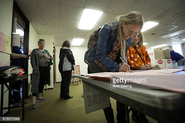 Julie Dickson signs in to vote as her daughter Gwen watches at Trinity Baptist Church on Super Tuesday March 1 2016 in Oklahoma City Oklahoma voters...