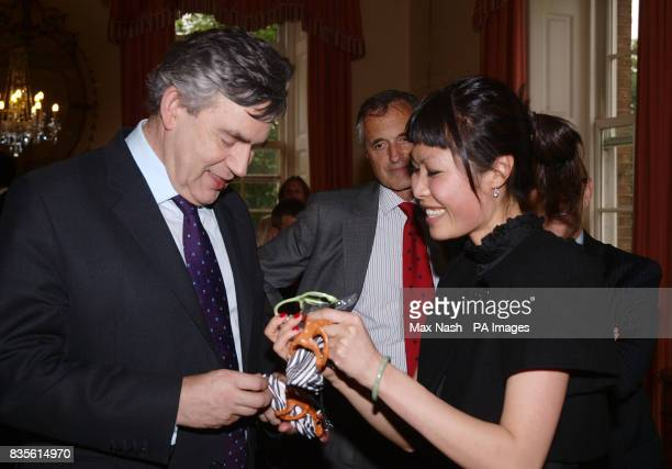 Julie Diem Le gives Prime Minister Gordon Brown two pairs of sunglasses for his children at a reception for entrepreneurs and business leaders at...