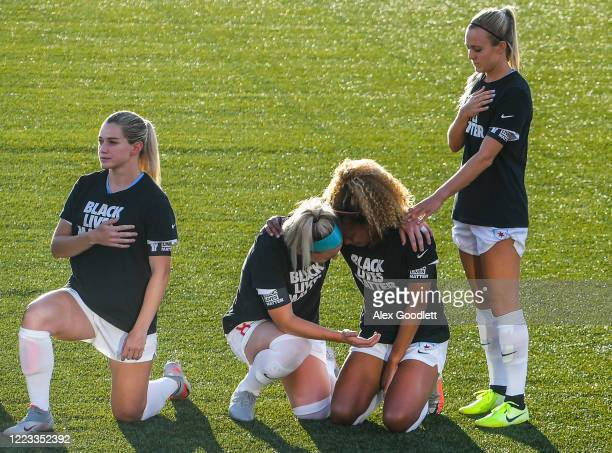 Julie Ertz and Rachel Hill hold Casey Short of the Chicago Red Stars kneel during the playing of the national anthem prior to a game against the...