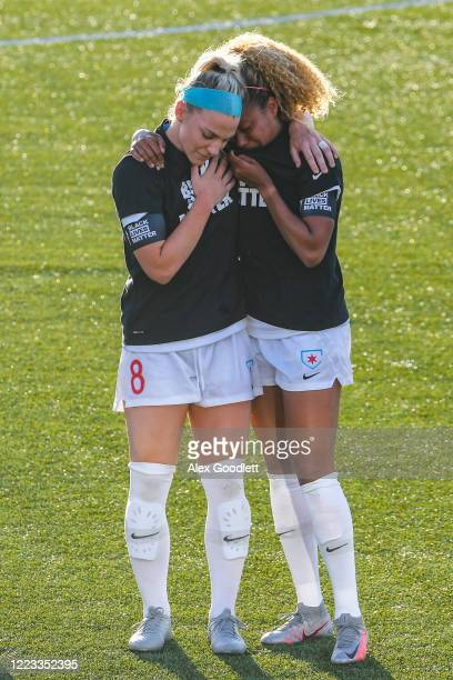 Julie Ertz holds Casey Short of the Chicago Red Stars react after the playing of the national anthem prior to a game against the Washington Spirit in...