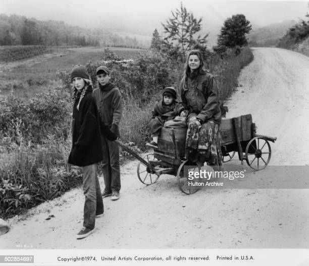 Julie Gholson and Matthew Burrill pull a wagon as Helen Harmon and Jan Smithers ride in the United Artist movie Where the Lilies Bloom circa 1974