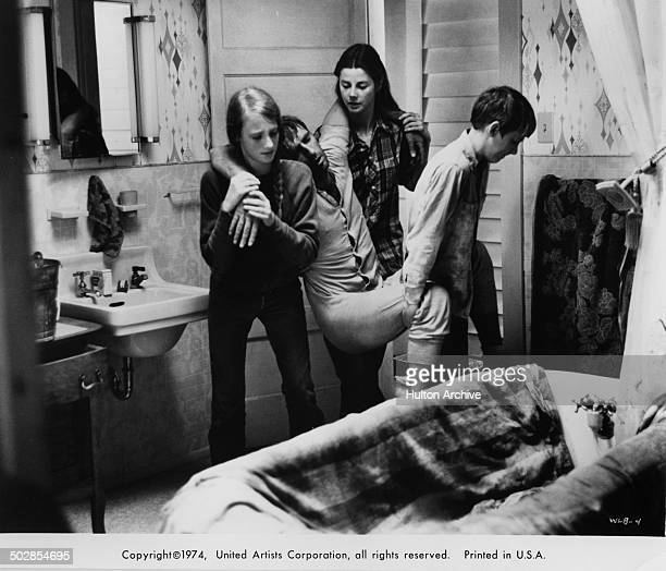 Julie Gholson Jan Smithers and Matthew Burrill carry pneumonia stricken Harry Dean Stanton in a scene for the United Artist movie Where the Lilies...