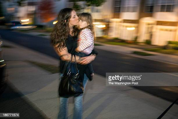 Julie Gloster, a single mother of three, kisses her daughter Sophie when she arrives home after work to her townouse in the Crossroads development in...