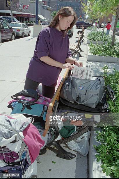 Julie Hanna removes outreach newletters from her possessions at a park bench on Charles St