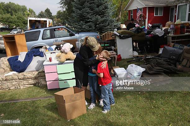 Julie Holzhauer embraces her children after they arrived home from school to find their family evicted from their home on September 15 2011 in...