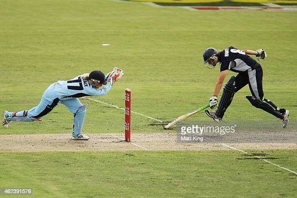 Julie Hunter of Victoria slides in to avoid a runout by Alyssa Healy of the Breakers during the Women's Twenty20 final match between New South Wales...