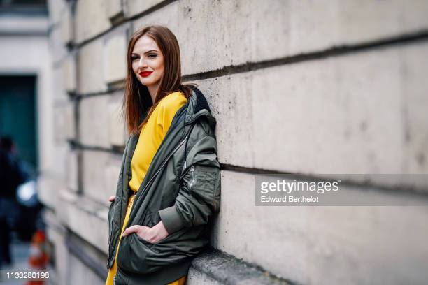 Julie Ianc wears a green khaki bomber jacket a yellow dress outside Elie Saab during Paris Fashion Week Womenswear Fall/Winter 2019/2020 on March 02...