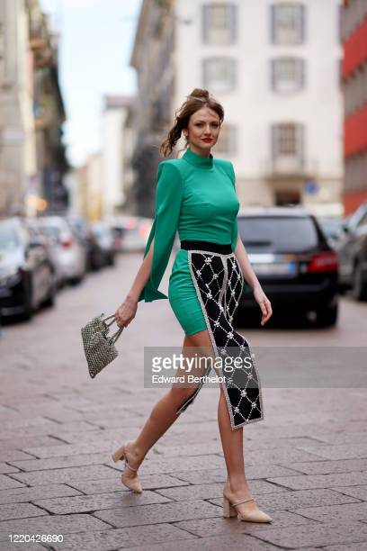 Julie Ianc wears a green turtleneck dress, a silver metallic mesh bag, pointy shoes, a beaded piece of outfit with pearls and argyle patterns,...