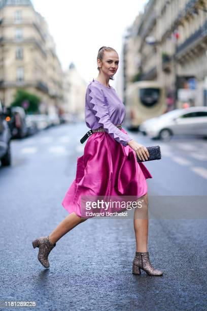 Julie Ianc wears a light purple longsleeves top a studded belt a lustrous hot pink flowing skirt a glittering black clutch glittering ankleboots...